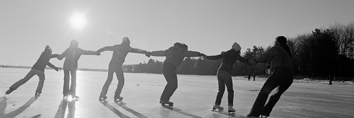 6 people all dressed in winter clothing with ice skates on a frozen lake. They are all holding hands and being pulled along by one another